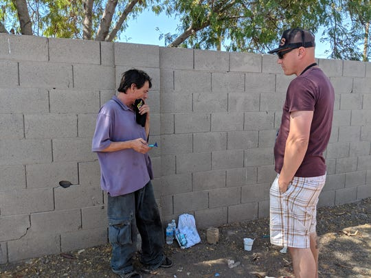 Brian Farretta of Phoenix Rescue Mission (right) converses with Juan Manuel Beltrán Rendón beside a liquor store in Phoenix.