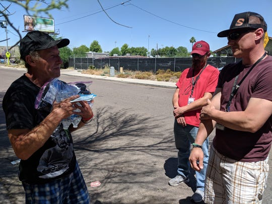 William Thompson (left) receives water and toiletries from Phoenix Rescue Mission. Thompson has been homeless on- and off-again for the past several years. During the summer, when people are most at risk for heat-related death, the Christian nonprofit distributes water and toiletries to homeless people in the Phoenix area. May 3, 2019. Priscilla Totiyapungprasert / The Republic.