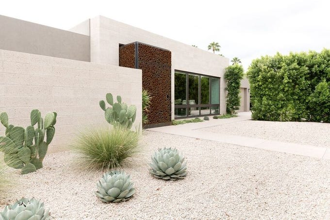 The four-bedroom, three bath house was renovated with a minimalistic, modern design. A row of Ficus trees provide privacy and sophistication.