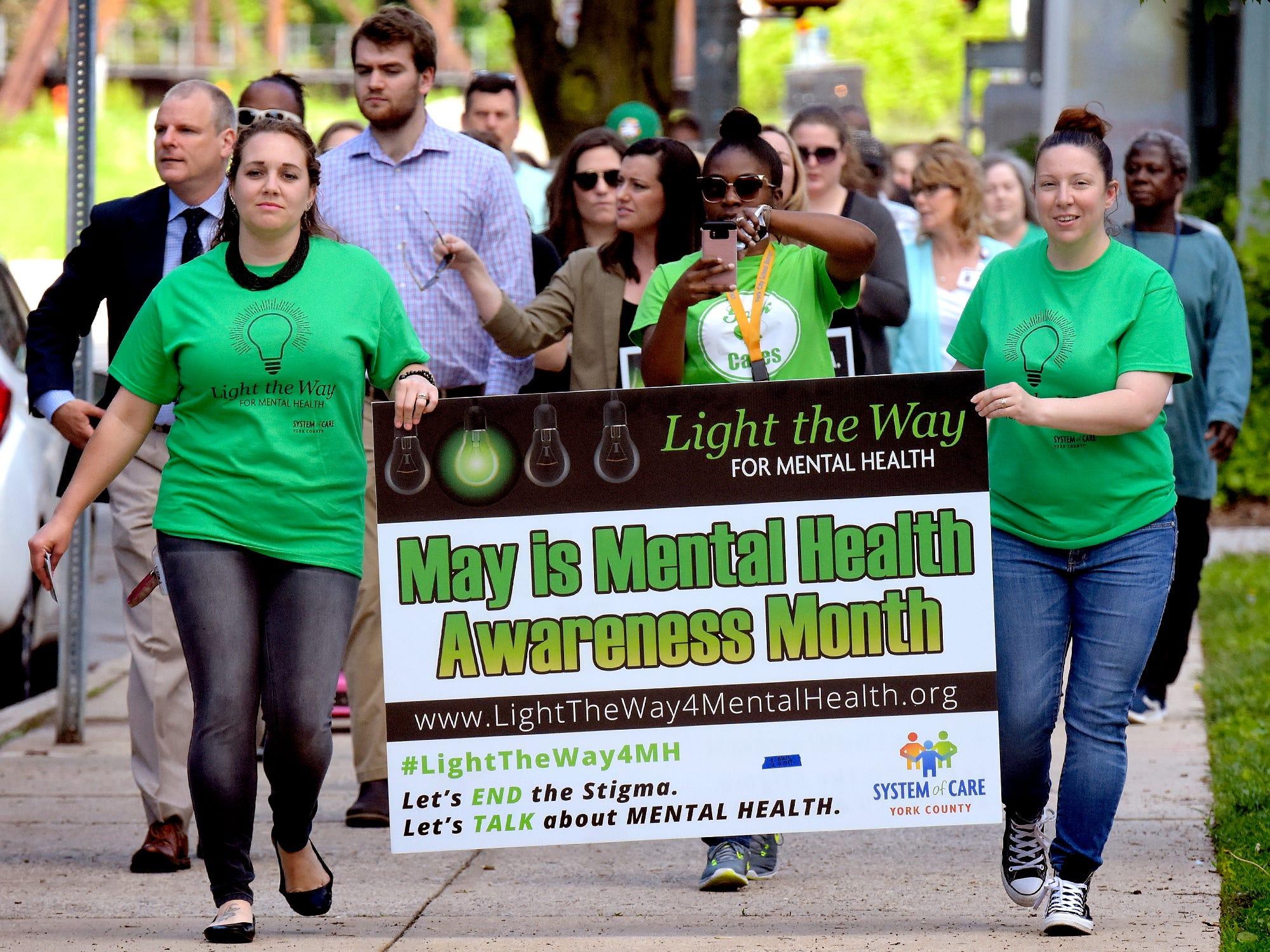 York County Human Services employees Kristin Hartman, left, and Victoria Valdes carry a sign during the Walk To Raise Awareness About Mental Health in York City Monday, May 6, 2019. The York County System of Care in collaboration with York County Human Services sponsored the walk during Mental Health Awareness Month. Area business and organizations will be displaying green lighting through May 12th to show support. Bill Kalina photo