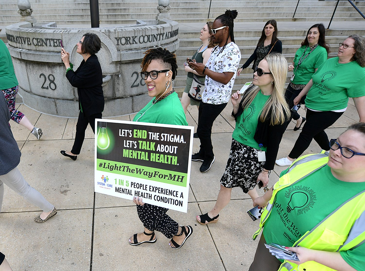 York County Human Services employee Endi Dabney-Cox carries a sign during the Walk To Raise Awareness About Mental Health as it passes the York County Administration Building in York City Monday, May 6, 2019. The York County System of Care in collaboration with York County Human Services sponsored the walk during Mental Health Awareness Month. Area business and organizations will be displaying green lighting through May 12th to show support. Bill Kalina photo