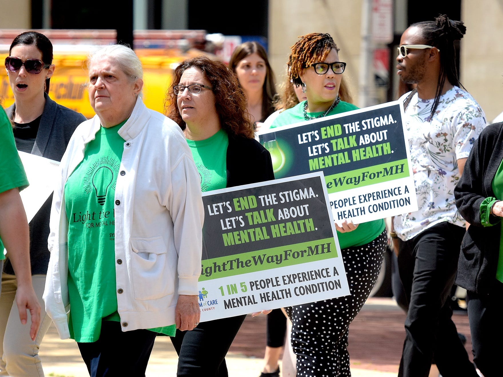 York County Human Services employees Del Franz, left, and Endi Dabney-Cox carry signs during the Walk To Raise Awareness About Mental Health in York City Monday, May 6, 2019. The York County System of Care in collaboration with York County Human Services sponsored the walk during Mental Health Awareness Month. Area business and organizations will be displaying green lighting through May 12th to show support. Bill Kalina photo