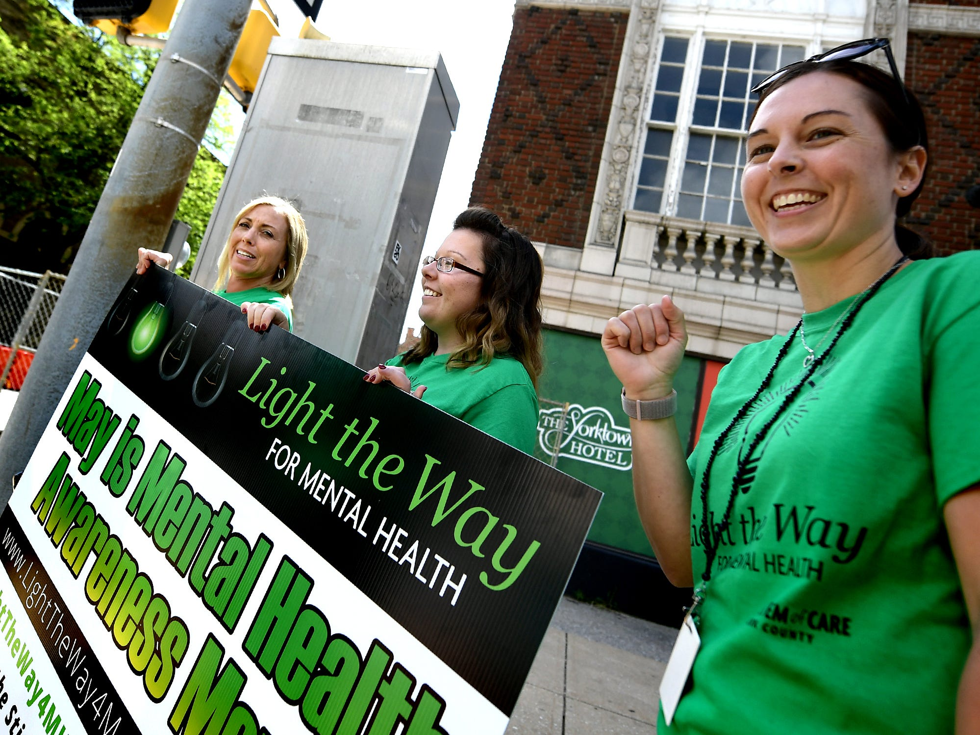 York County Human Services employees, from left, Tiffani Kleiser, Tiffany Sager and Dawn Hopkins cross Market Street during the Walk To Raise Awareness About Mental Health in York City Monday, May 6, 2019. The York County System of Care in collaboration with York County Human Services sponsored the walk during Mental Health Awareness Month. Area business and organizations will be displaying green lighting through May 12th to show support. Bill Kalina photo