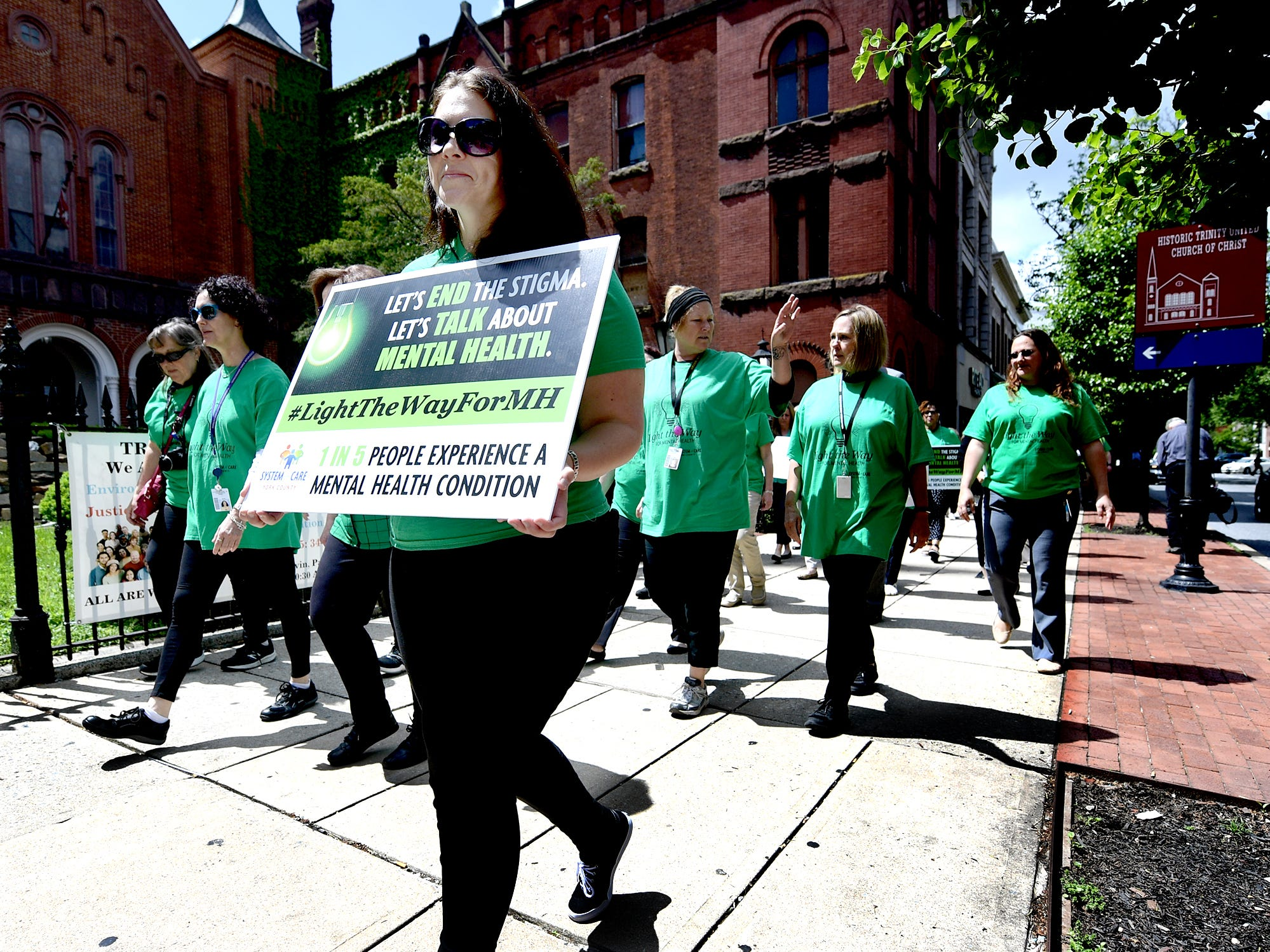 Marchers, many who are York County Human Services employees, participate in the Walk To Raise Awareness About Mental Health in York City Monday, May 6, 2019. The York County System of Care in collaboration with York County Human Services sponsored the walk during Mental Health Awareness Month. Area business and organizations will be displaying green lighting through May 12th to show support. Bill Kalina photo
