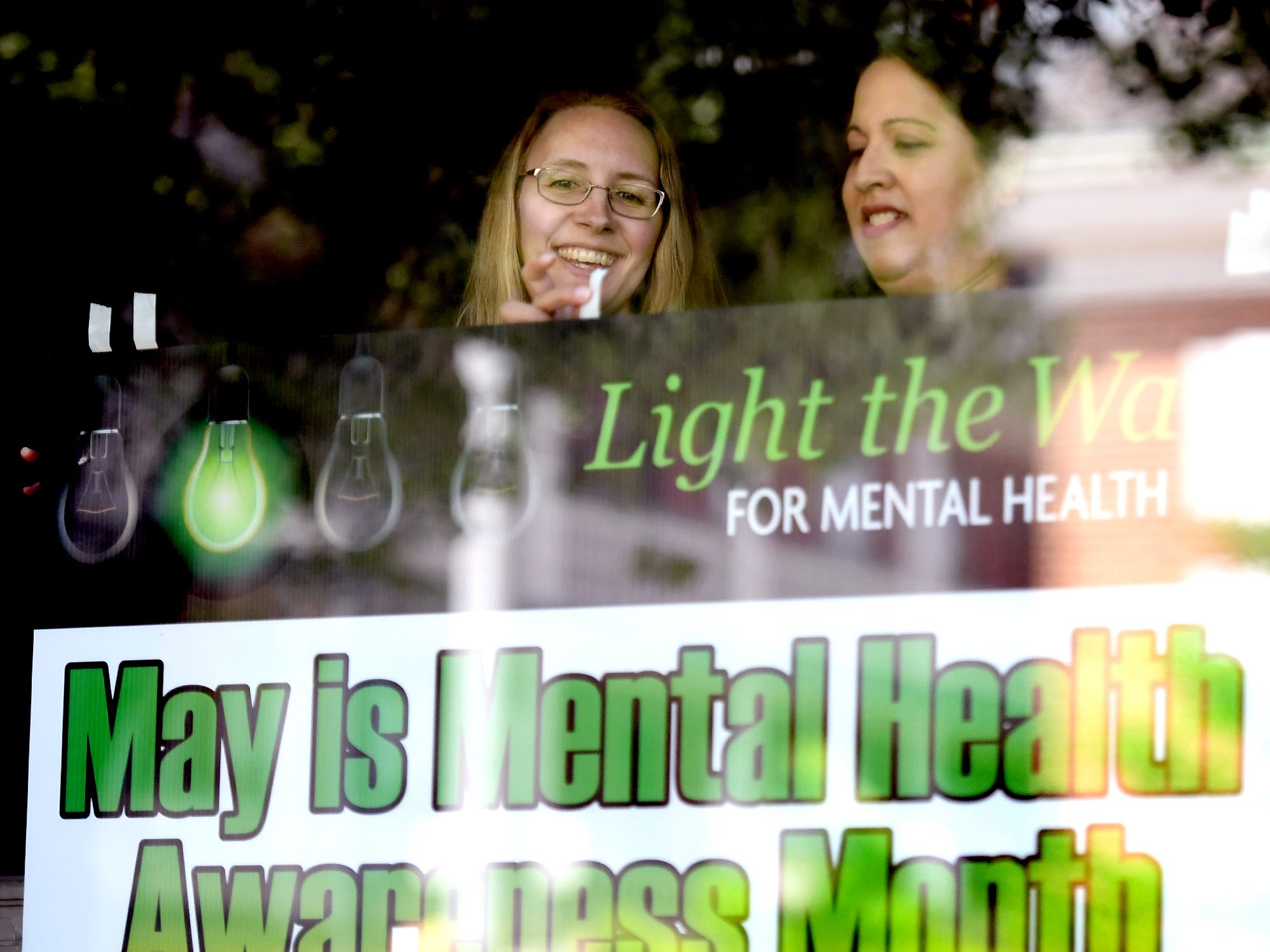 York County Human Services employees Nikki Miller, left, and Pam Bhalla hang a sign before the Walk To Raise Awareness About Mental Health in York City Monday, May 6, 2019. The York County System of Care in collaboration with York County Human Services sponsored the walk during Mental Health Awareness Month. Area business and organizations will be displaying green lighting through May 12th to show support. Bill Kalina photo