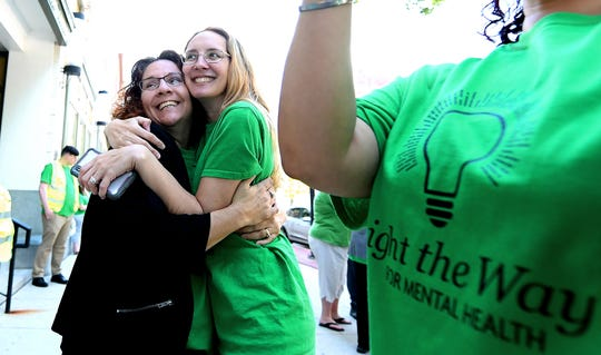 York County Human Services employees Del Franz, left, and Nikki Miller embraces after the Walk To Raise Awareness About Mental Health in York City Monday, May 6, 2019. The York County System of Care in collaboration with York County Human Services sponsored the walk during Mental Health Awareness Month. Area business and organizations will be displaying green lighting through May 12th to show support. Bill Kalina photo
