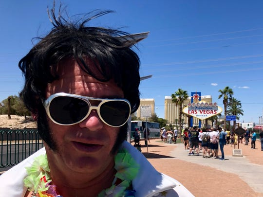"An Elvis Presley impersonator near the ""Welcome to Fabulous Las Vegas"" sign."