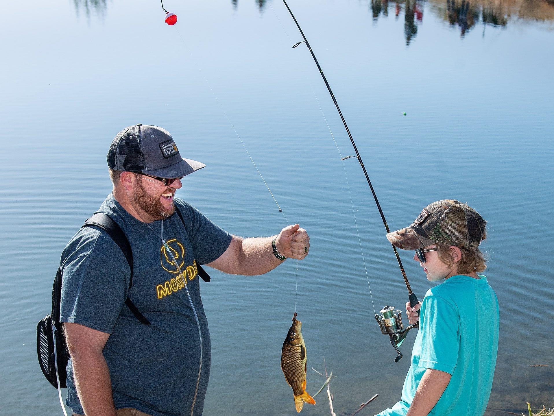 Layton Galvin, 9, and his stepdad Jason Booth examine LaytonÕs catch.