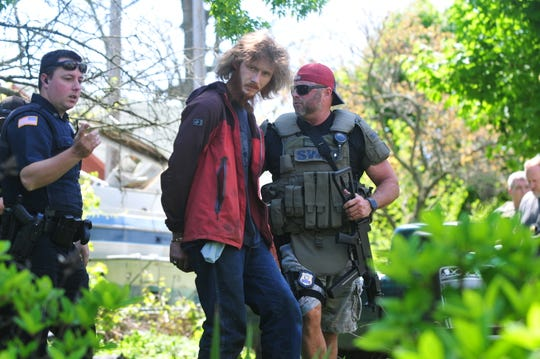 Lt. Scott Crull (right) and Officer Zach Taylor escort Brandon Winters from the back yard at 225 N. 12th St. after Winters was detained when a search warrant was executed.