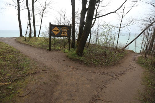 Signs warn hikers to stay away from trail along the bluff.