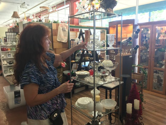 Pam Komar, known as the Glass Lady, shows off some of her merchandise inside Oregon Street Antique Mall. Komar will move her business to The Red Door on East Cypress Avenue.