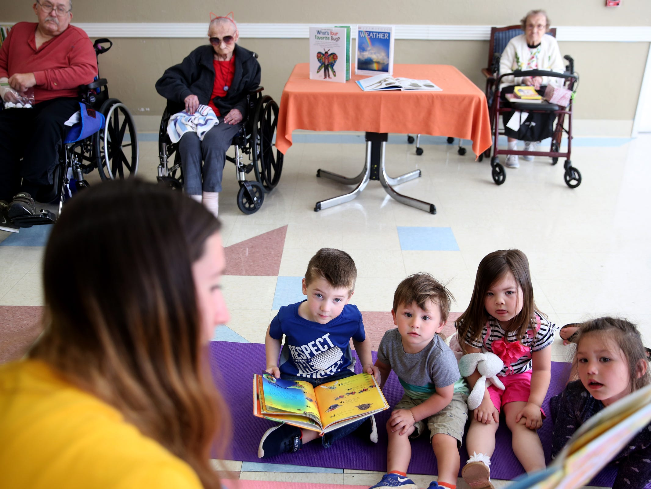 "Hank Jacobs, 5, Mateo Pineda, 2, Zora Thaggard, 3, and Eva Pineda, 4, listen as Makenzie Pineda reads a book to them during a visit by the Friendship Brigade, a group that focuses on intergenerational programming, at Avamere Transitional Care at Sunnyside in Salem on May 6, 2019. Once a week, ""Storytime at Sunnyside"" brings preschoolers to the seniors for reading, singing, dancing and other playtime activities."