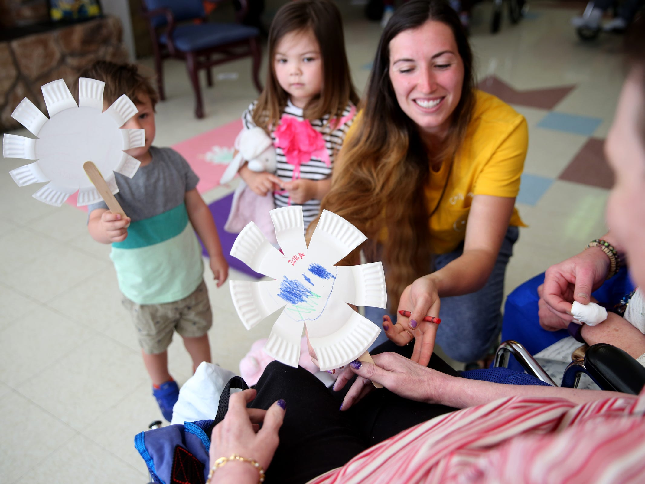 "Makenzie Pineda helps Mateo Pineda, 2, and Zora Thaggard, 3, give paper plate shaped like flowers they had colored to a woman during a visit by the Friendship Brigade, a group that focuses on intergenerational programming, at Avamere Transitional Care at Sunnyside in Salem on May 6, 2019. Once a week, ""Storytime at Sunnyside"" brings preschoolers to the seniors for reading, singing, dancing and other playtime activities."