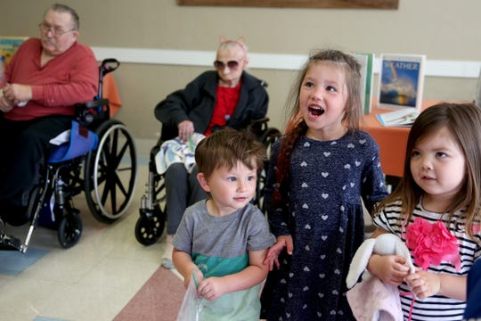 """Mateo Pineda, 2, Eva Pineda, 4, and Zora Thaggard, 3, all listen to a story during a visit by the Friendship Brigade, a group that focuses on intergenerational programming, at Avamere Transitional Care at Sunnyside in Salem on May 6, 2019. Once a week, """"Storytime at Sunnyside"""" brings preschoolers to the seniors for reading, singing, dancing and other playtime activities."""