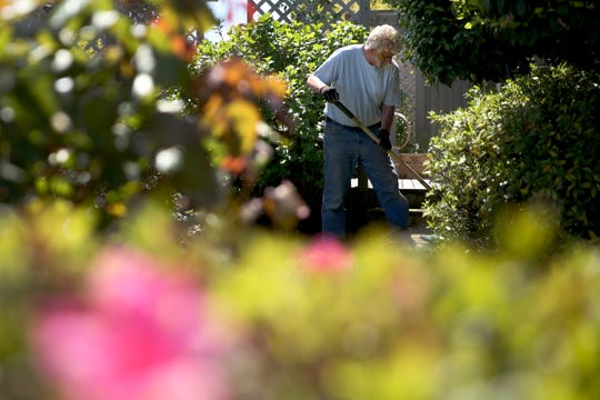 """Larry Mattson checks an irrigation line and prepares his flower garden for the season at his Salem home on May 6, 2019. Temperatures this week are expected to reached the upper 80s, about 20 degrees above normal for this time of year. """"We welcome the warm weather,"""" Mattson said, who has maintained a large garden with his wife at their home for about the last 40 years."""