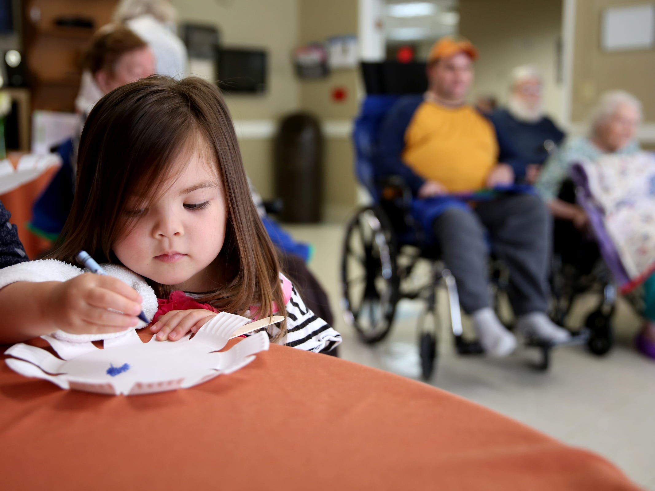 "Zora Thaggard, 3, colors during a visit by the Friendship Brigade, a group that focuses on intergenerational programming, at Avamere Transitional Care at Sunnyside in Salem on May 6, 2019. Once a week, ""Storytime at Sunnyside"" brings preschoolers to the seniors for reading, singing, dancing and other playtime activities."