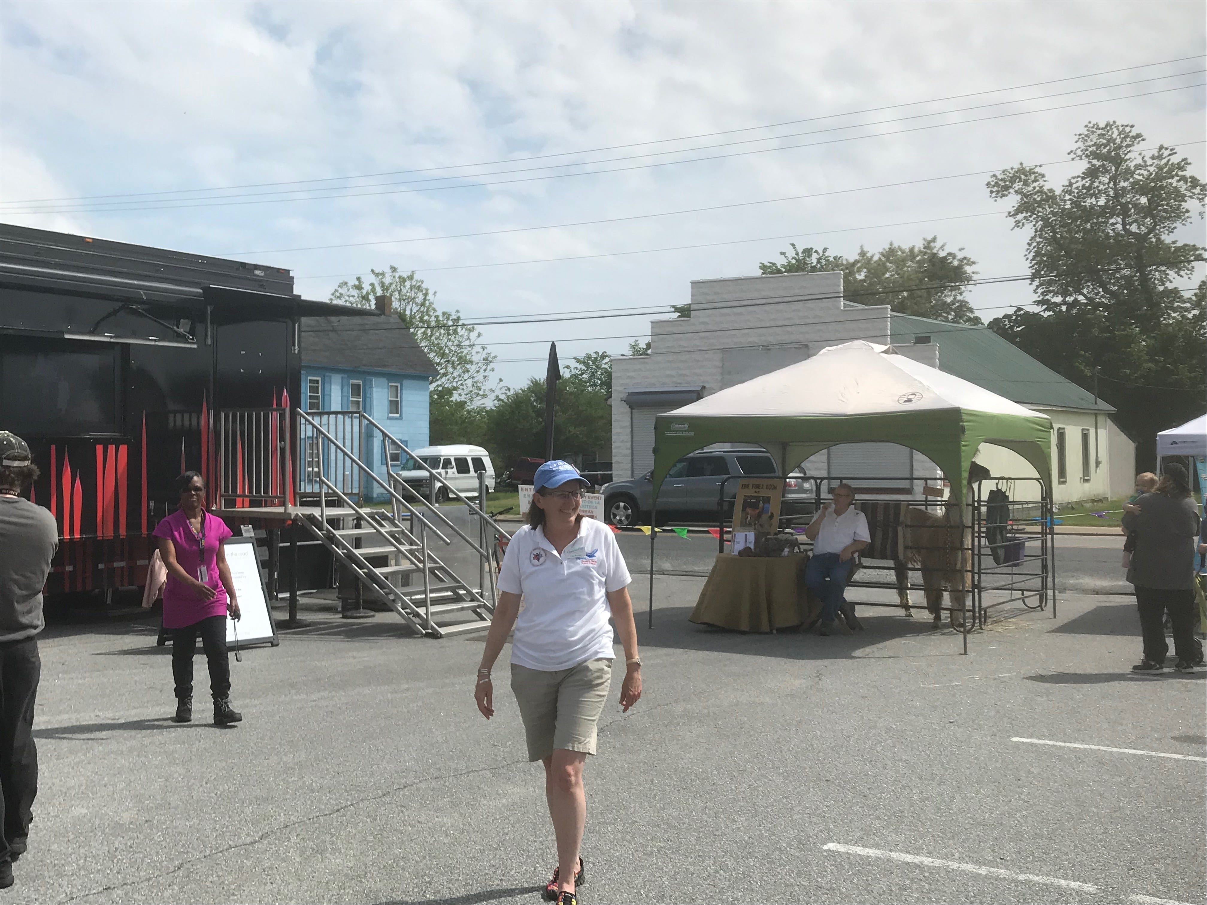 """Cara Burton, Eastern Shore Public Library director, walks near the Virginia Museum of Fine Arts' artmobile during  a multicultural festival, 'Celebrate Us,"""" at the site of the future regional library in Parksley, Virginia on Sunday, May 5, 2019."""