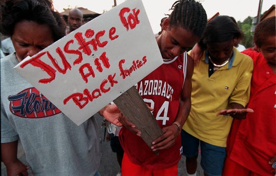 Terry White holds a sign while praying with others during last night's gathering at the scene of Wednesday's fatl shooting of a man by police. Times photo/Chris Stanfield 8/5/99
