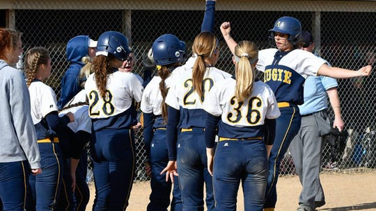 Augustana's Maggie Kadrlik is greeted at home plate by her teammates after a home run