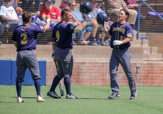 Augustana's Riley Johnson (22) celebrates a run with Will Olson (9)