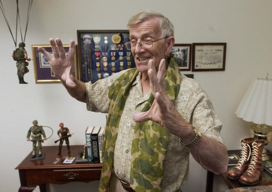 World War II veteran Ralph Manley talks of his experiences as a paratrooper on D-Day. A peice of his parchute around his neck and his combat boots on the table behind, Manley describes some of his experiences in the war from his Springfield office. Bob Linder/News-Leader