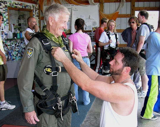 Tandem skydive Instructor Terry Wendt, of Rogersville, helps Springfield Mayor Pro Tem Ralph Manley on with his harness. The 81-year-old Manley and his friend, Elmer Lewis, 88, took a tandem jump Friday at the eighth annual Hillbilly Boogie. Credit: Steve Brigman.