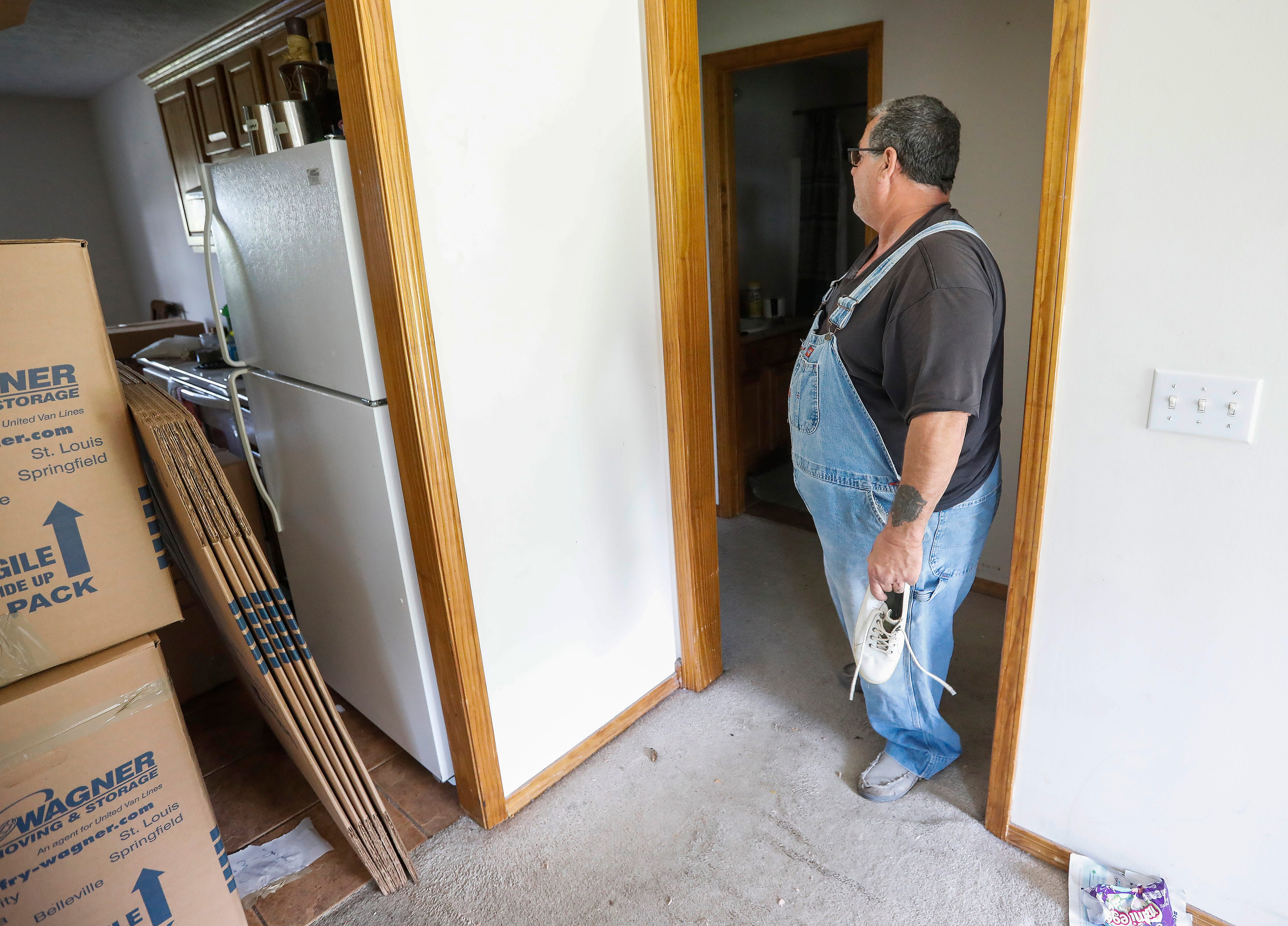Joe Rossi looks into the bathroom in the hallway that he and his wife crawled into to seek shelter from a tornado that hit their house in Ozark on May 30, 2019.