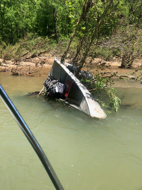The Jacks Fork River was closed to paddlers when this boat capsized and was bent around a tree.