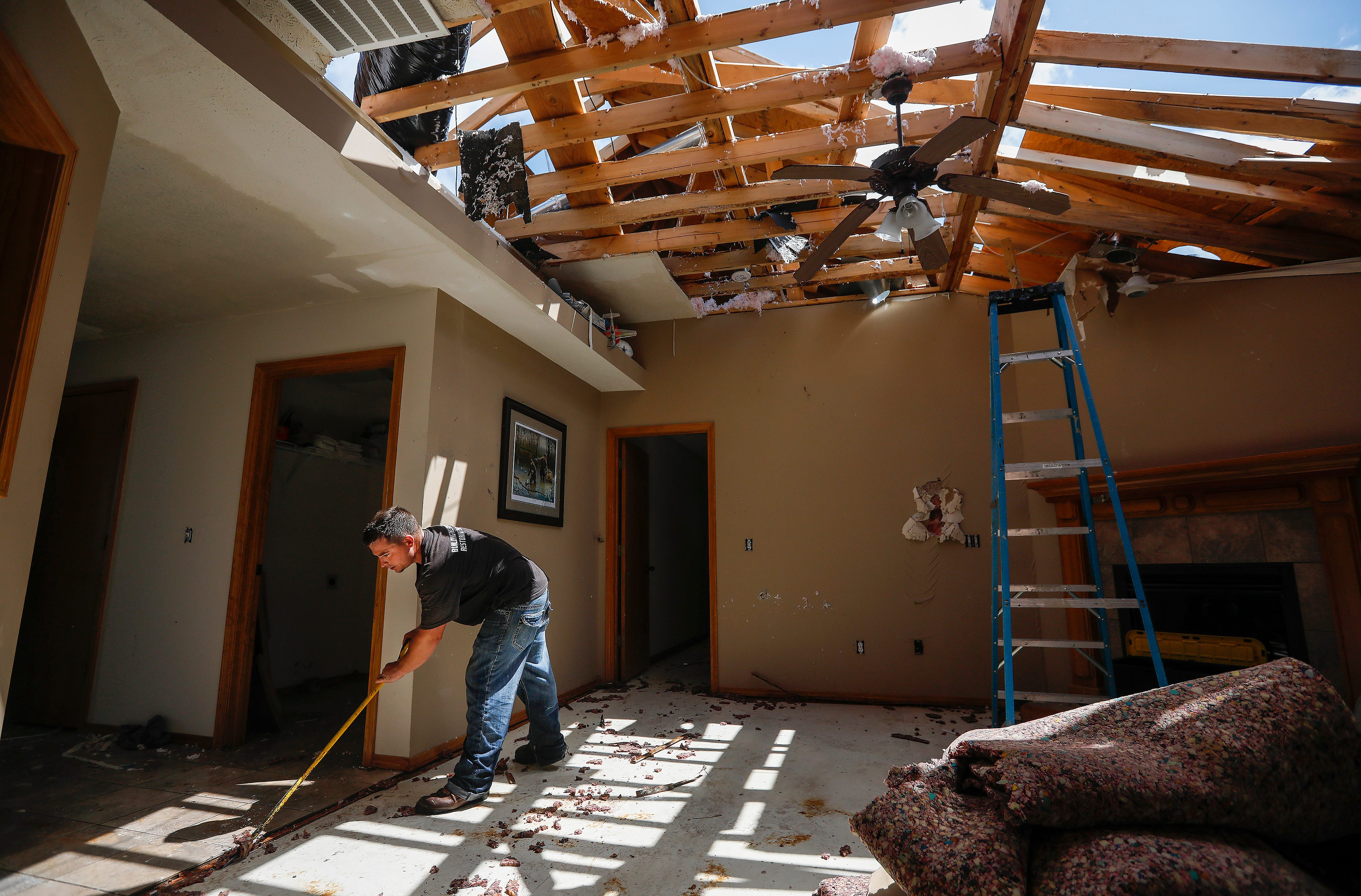 Ryan Payne, of Solutions Systems, works on restoring a home that  was damaged by a tornado that moved through Ozark on May 30, 2019.