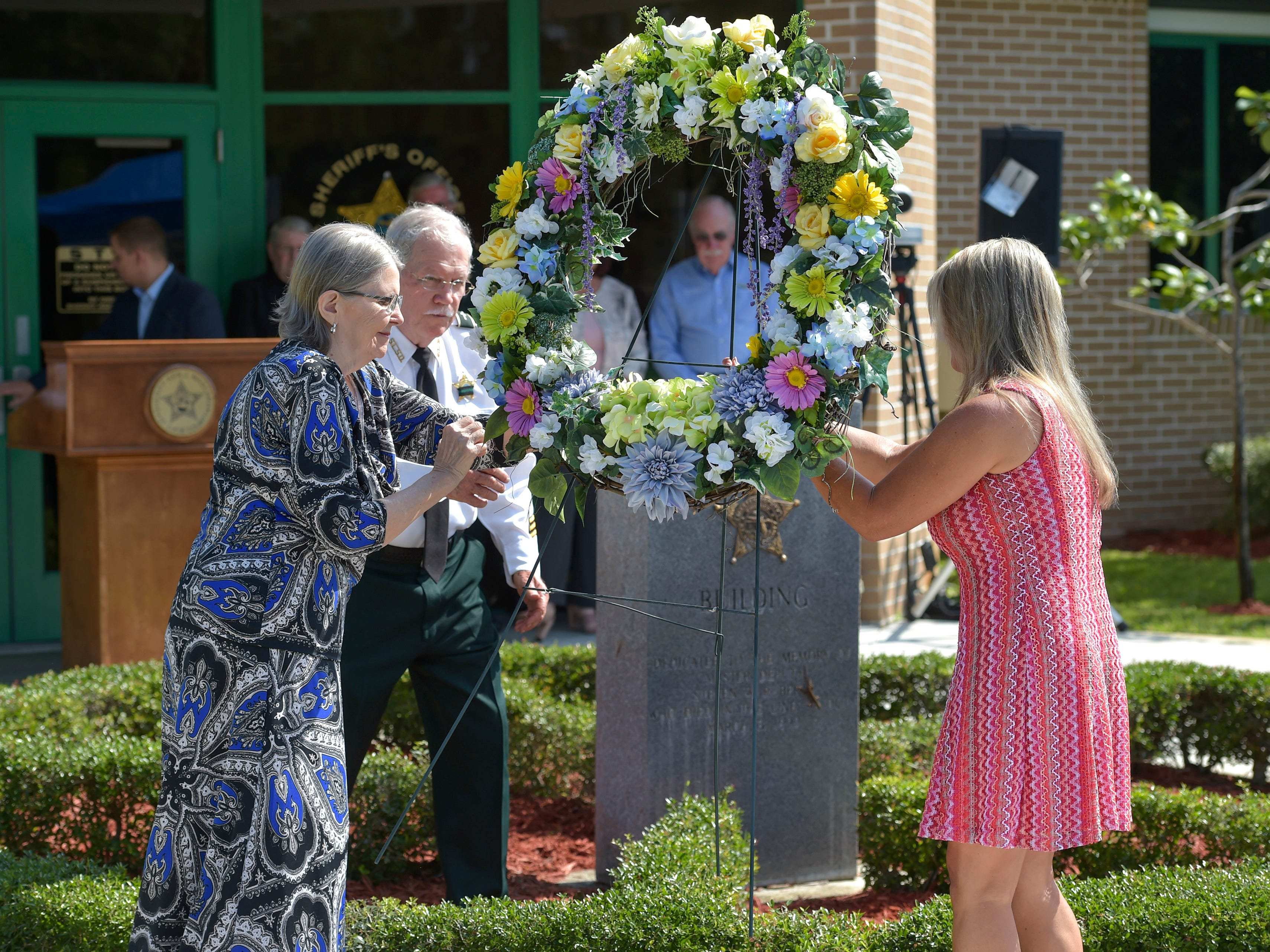Margaret Hover-Runnion (left), wife of the late Master Deputy Joseph Hover, and Tonya Scavuzzo, wife of the late Captain Charlie Scavuzzo, position a memorial wreath of remembrance with the help of Chaplain David Thompson (second from left) during the St. Lucie County Sheriff's Office Laying of the Wreath Service for their fallen deputies for National Law Enforcement Memorial Week at the sheriff's office Master Deputy Steve Roberts Building on Monday, May 6, 2019, in Fort Pierce. The St. Lucie County Sheriff's Office memorial honored the eight heroes and one K9 that gave their lives serving the community of St. Lucie County. The service was held a week prior to the official National Police Week, due to Captain Charlie Scavuzzo being added to the National Law Enforcement Memorial Wall in Washington D.C. on May 13, and also his being recognized at the annual National Peace Officer's Memorial Service on the lawn of the U.S. Capitol on May 15.