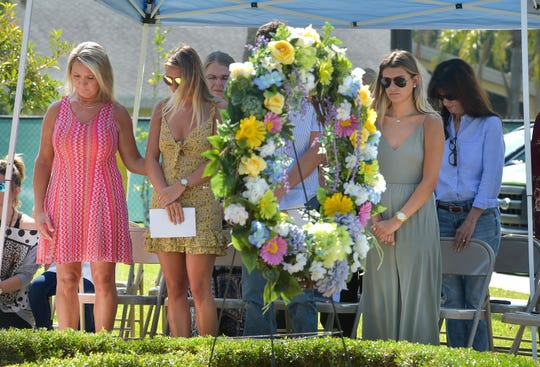 """Tonya Scavuzzo (front row, from left), wife of the late St. Lucie County Sheriff's Office Captain Charlie Scavuzzo, and their daughters Lyndsey Scavuzzo, 18, and Sydney Scavuzzo, 22, are seen behind a memorial wreath during the playing of Taps at the St. Lucie County Sheriff's Office's Laying of the Wreath Service for National Law Enforcement Memorial Week on Monday, May 6, 2019, in Fort Pierce. That service honored the sheriff's office's eight heroes and one K9 that gave their lives while serving the community in St. Lucie County. """"It's a huge honor for Charlie. He deserves it. He's very deserving of this,"""" Tonya Scavuzzo said. """"He deserves to be in Washington, his whole life and career was this."""" Captain Charlie Scavuzzo's name is being added to the National Law Enforcement Memorial Wall in Washington D.C., and is being recognized at the annual National Peace Officer's Memorial Service on the lawn of the U.S. Capitol on May 15."""