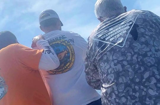 Michael Bramhall, Jared Buchanon and Ron Buchanon lean over the bow of Ron Buchanon's Pathfinder in order to observe a large great white shark for a few minutes. The shark was seen about five miles off Fort Pierce Sunday.