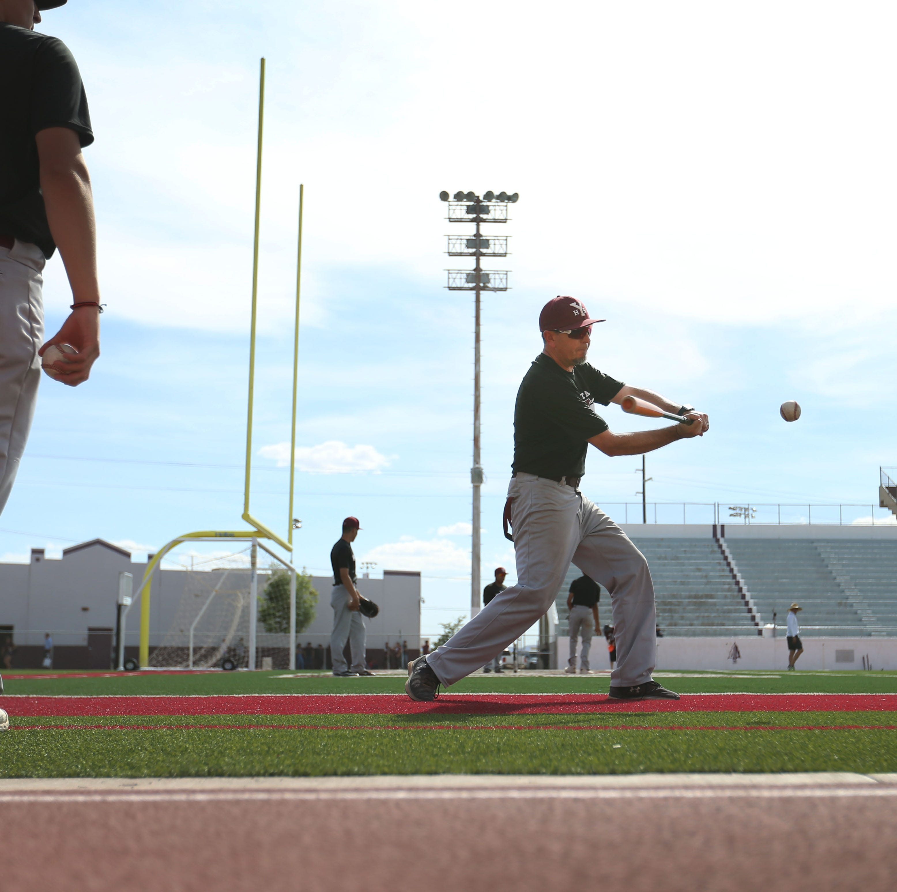 Ysleta baseball coach Rene Solis takes the infielders to the football field to practice grounders Monday, May 6, 2019, in El Paso. Solis had the team practice fielding grounders on the football field since some of the teams they are going to play have turf fields.