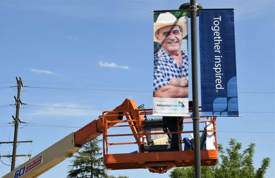 """Crews work to install  """"Adventist Health Tulare"""" signs in the Tulare hospital's parking lot after officials approved the name change late last month."""