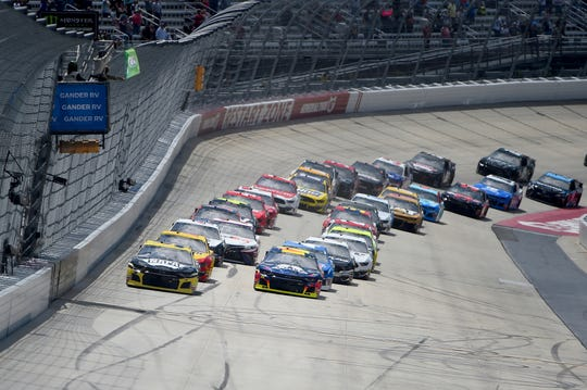 Driver Chase Elliott (9), left, leads as drivers take the green flag during the NASCAR Cup Series auto race, Monday, May 6, 2019, at Dover International Speedway in Dover, Del.