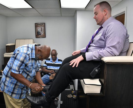 Dustin O'Donnell watches as Tyrone Kimbel, left, begins buffing his shoes as Ronny Caldwell works on a loafer at Wichita Boot and Shoe Care Center in the lobby of the City National Building.