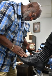 Tyrone Kimbel rubs a conditioner into leather as he works on a customer's shoes at Wichita Boot and Shoe Care Center.