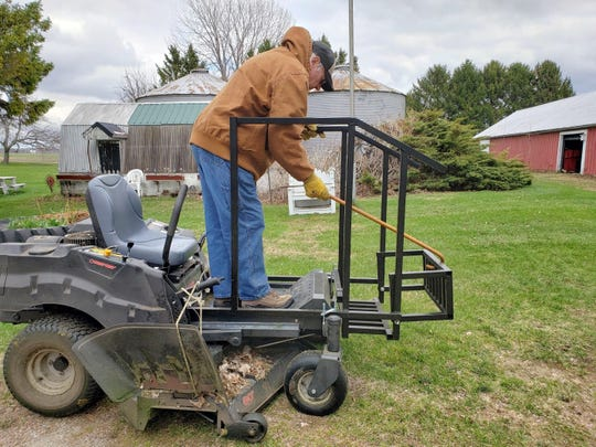 Bob pulls up mower step with his cane.