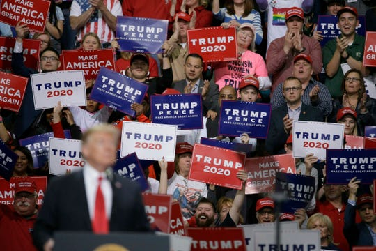 President Donald Trump speaks at a Make America Great Again rally as supporters hold up signs, April 27, 2019, in Green Bay, Wisconsin.