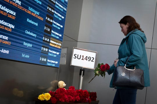 A woman places flowers at the sign of the last flight of the Sukhoi SSJ100 aircraft of Aeroflot Airlines.