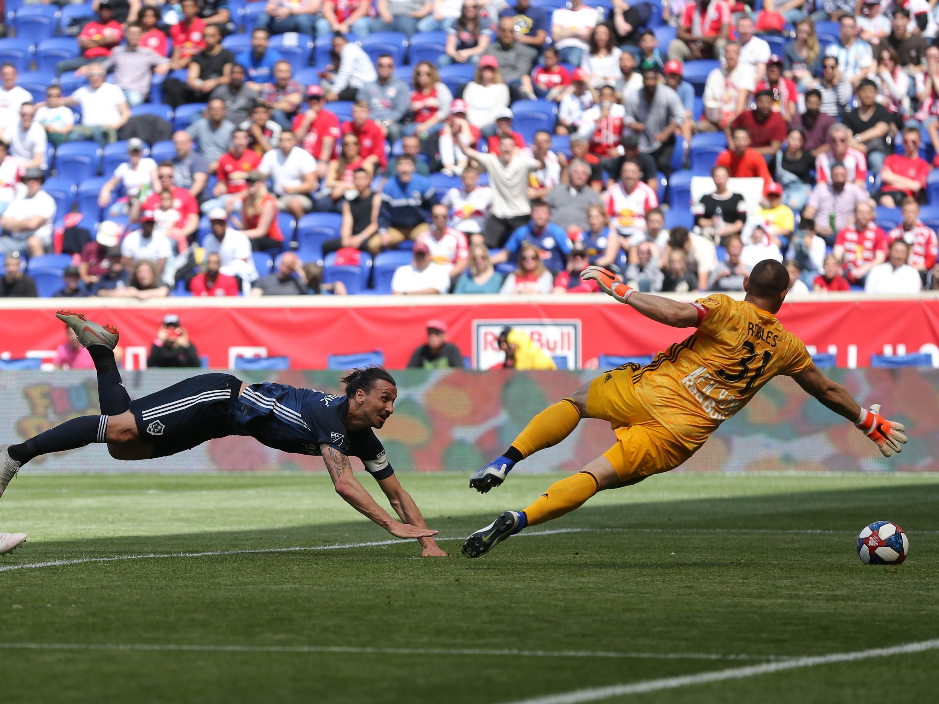 May 4: LA Galaxy forward Zlatan Ibrahimovic heads the ball past New York Red Bulls goalie Luis Robles for a goal during the first half at Red Bull Arena. RBNY won the game, 3-2.