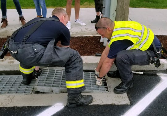 Firefighters remove a grate from a catch basin along a street near the chemistry building on the UConn campus in Storrs, Conn.
