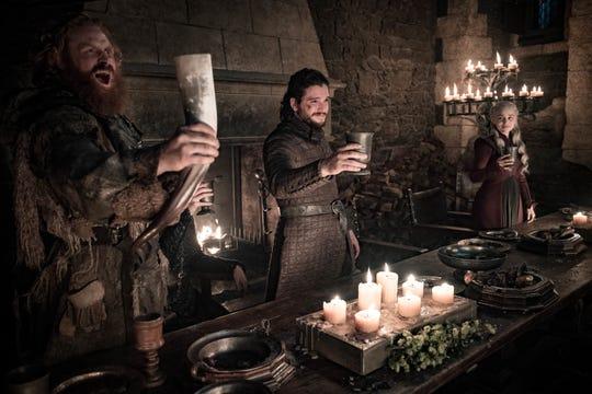 Tormund Giantsbane (Kristofer Hivju), left, Jon Snow (Kit Harington) and Daenerys Targaryen (Emilia Clarke) toast victory at the Battle of Winterfell.