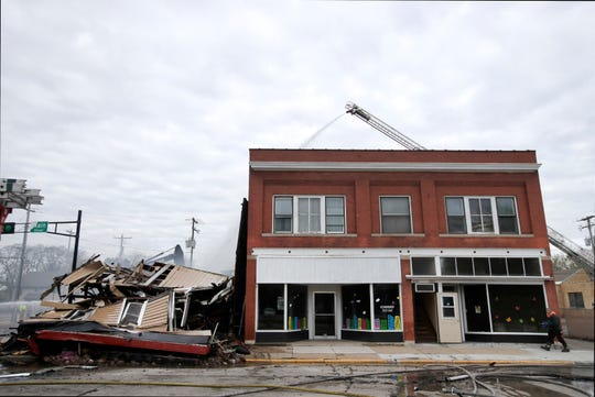Firefighters continue to work at the scene of a fire destroyed that Mabel Murphy's bar May 7, 2019, in Oshkosh, Wis.