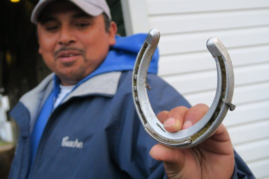 """Jose """"Guache"""" Hernandez holds a shoe from Maximum Security, disqualified after winning the Kentucky Derby on Saturday, that came loose during his trip to Monmouth Park early Tuesday, May 7, 2019."""