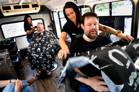Aspin Santos shakes a barber's cape over Jason Lingnau as Sondra Martinez continues cutting Hugh Cromwell's hair Tuesday. The two were cutting hair inside a converted van called Curbside Cuts on South First Street, offering free cuts to veterans, first-responders and military members.