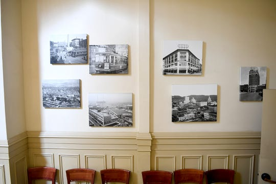 Historic photographs of Asheville hang on a wall inside the Flatiron Building downtown.
