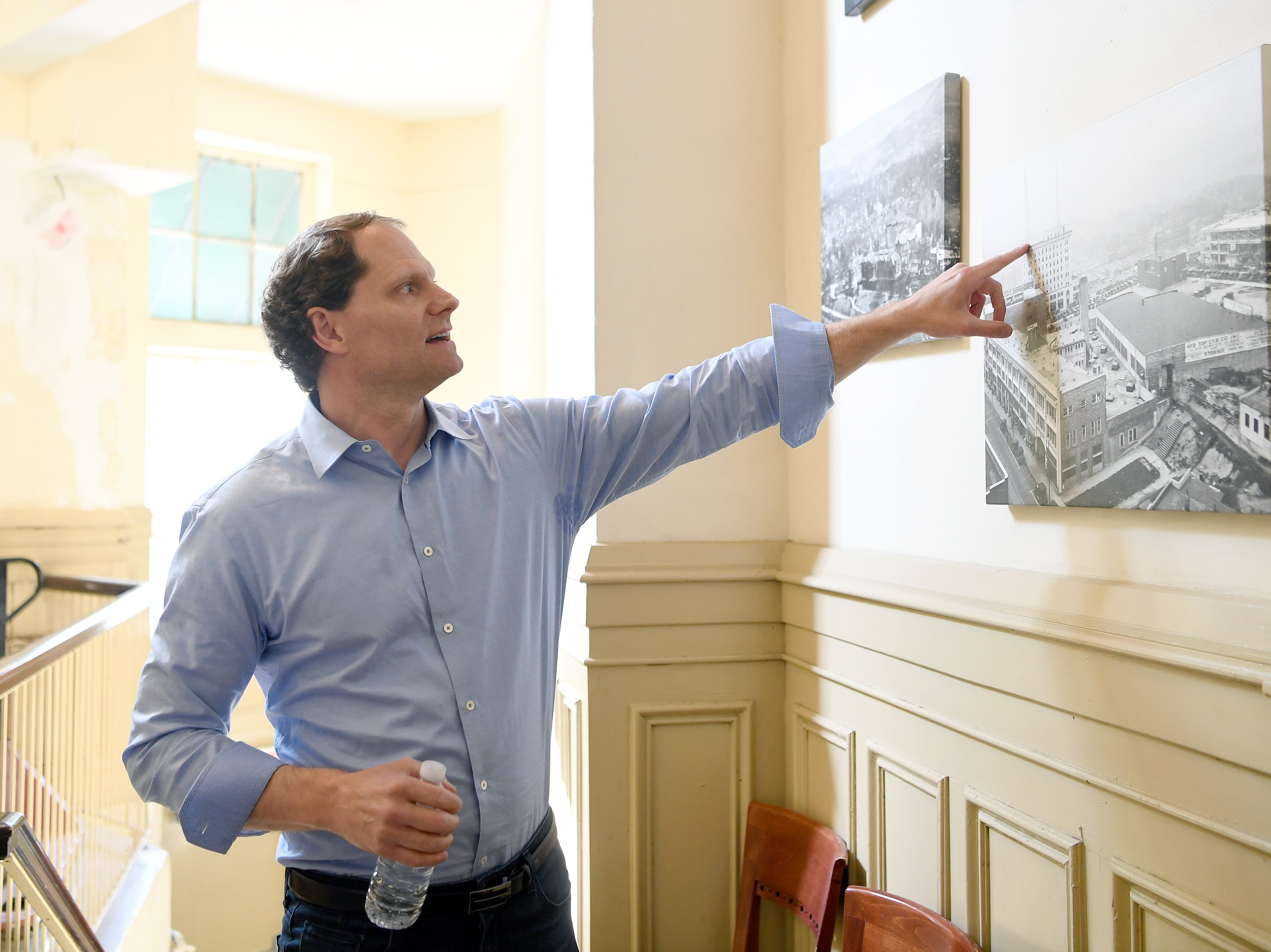 Developer Philip Woollcott, of the Flatiron Preservation Group, points out old features of the Flatiron Building in an historic photograph during a tour on May 3, 2019. Woollcott is waiting final approval to preserve the building and turn it into an 80-room boutique hotel.