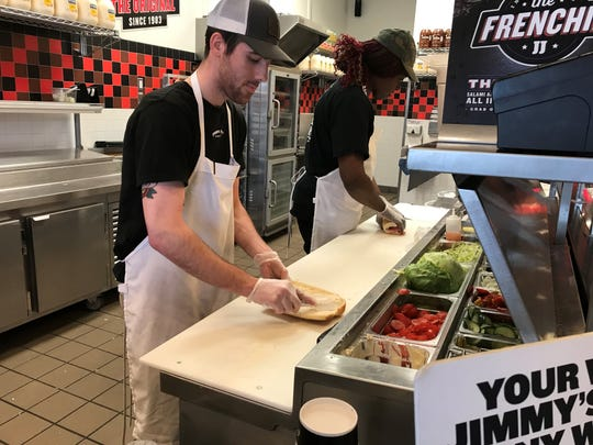 Workers Jacob Nigg (left) and Jamekia Vines prepare sandwiches at the Jimmy John's restaurant on Beckley Road.