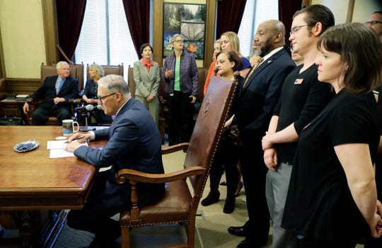 Washington Gov. Jay Inslee, left, signs Senate Bill 5205 into law Tuesday, May 7, 2019, as supporters look on at the Capitol in Olympia, Wash. The bill regulates firearms possession by people who have been found incompetent to stand trial and who have a history of one or more violent acts. The measure was one of several gun-related bills signed into law Tuesday.